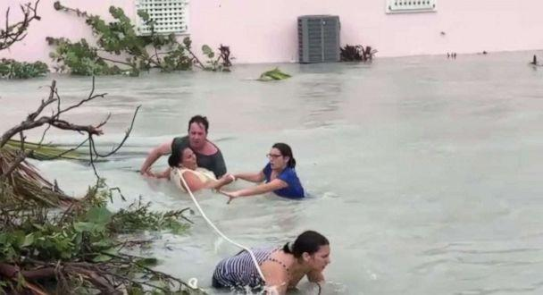 Dramatic video shows people in Bahamas swimming through rushing floodwaters